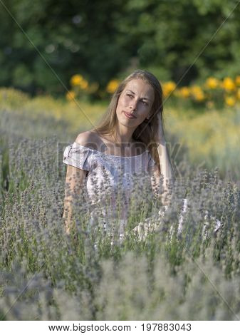 Beautiful woman in sunny day wearing pink dress and sitting in fresh lavander field, enjoying beauty of nature. Sto