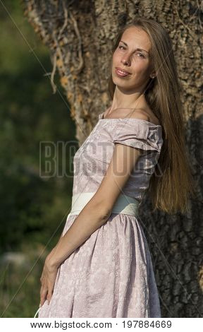 Beautiful woman portrait in a pink dress in front of a tree with ivy. Stock photo