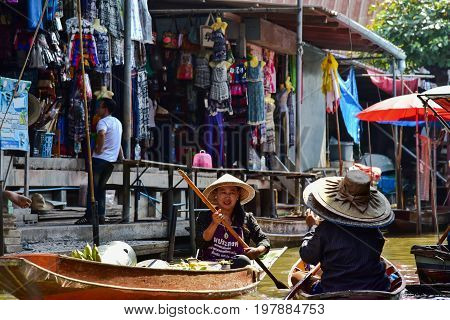 Bangkok / Thailand - January 20 2017: Thai women working in a boat in the floating market nearby Bangkok. Floating market is one of the main tourists attractions in Bangkok.