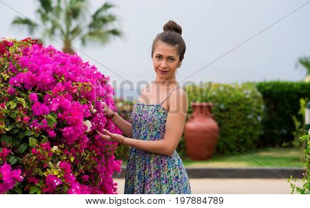 The color specialist checks the quality of the petals. Beautiful girl with a shingle posing near a big bush with flowers on a background of a Greek jug