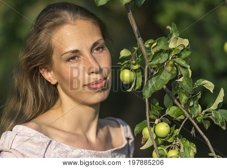 Portrait of a beautiful woman with apple tree branch with apples. Stock photo