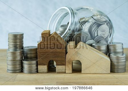 wooden miniature house with stack of coins and coins in glass jar as financial saving or mortgage concept.