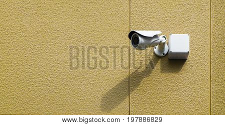 Infrared cctv camera on the exterior textured wall in yellow color with light and shadow selective focus.