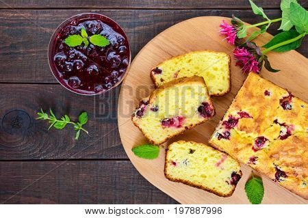 Delicate tasty curd cake with black currant and jam on a dark wooden background. Top view.