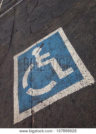 Disabled blue parking sign painted on dark asphalt.