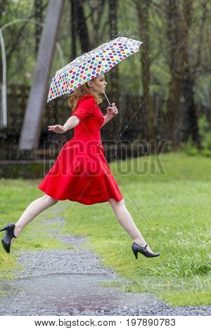A redhead model posing in an outdoor environment in the rain