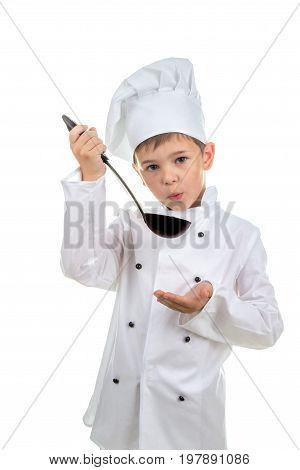 Small cute boy in chef's hat with ladle tastes the cooked soup.