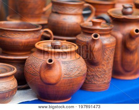 Ceramic teapots and mugs on the pottery fair. Ceramic tableware
