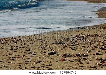 Sand coast with pebbles and ocean waves caressing the shore; sun litting the colourful pebbles