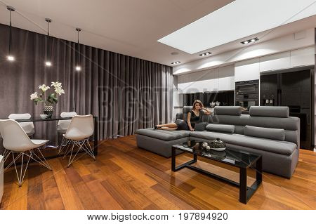 Woman lying on gray sofa in modern apartment with dining table chairs and kitchenette