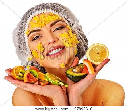 Facial mask from fresh fruits for woman. Girl in medical hat give slices of avocado, grapefruit and kiwi as ingradients for face care smooth skin on isolated. Mask against sagging skin.