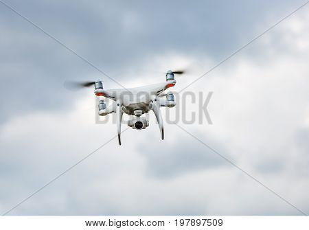 Quadrocopter drone hovers in the sky. Drone quad copter. Flying unmanned camera.