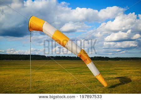 Striped orange and white windsock against blue sky with clouds and field of grass.