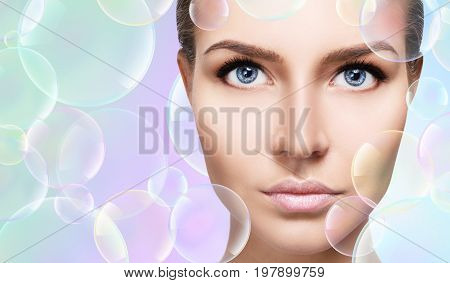 Beautiful sensual woman in soap bubbles over colorful background. Cleansing concept.