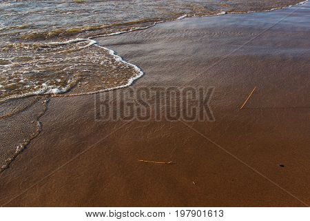 A background of a sandy beach with a receding wave