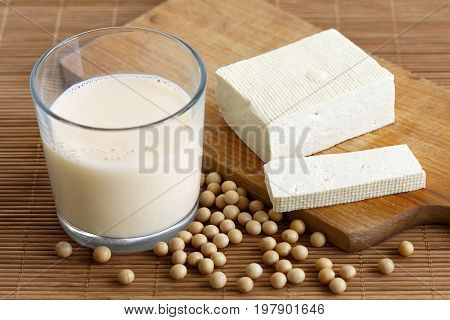 Glass Of Soya Milk With Froth On Bamboo Mat With Spilled Soya Beans. Next To Cut Tofu Block.