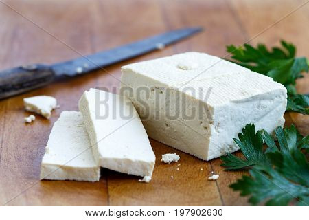 Single Block Of White Tofu With Two Tofu Slices, Crumbs, Fresh Parsley And Rustic Knife On Wooden Ch