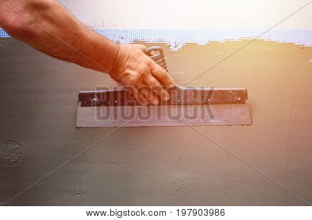 Hands Of An Old Manual Worker With Wall Plastering Tools Renovating House. Plasterer Renovating Outd