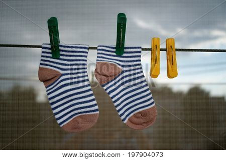 Baby socks after washing on a string with colorful clothespins