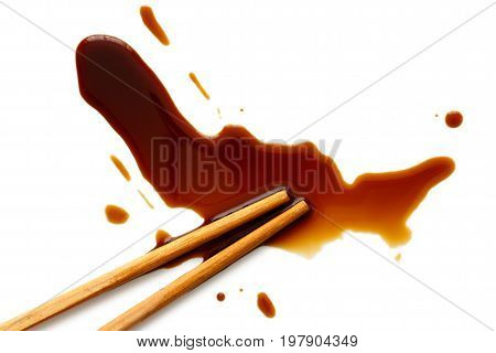 Spilled soya sauce on white with wooden chopsticks from above.