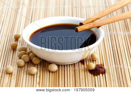 Soya Sauce In White Bowl On Bamboo Mat With Chopsticks Resting On The Bowl And Spilled Soya Beans An