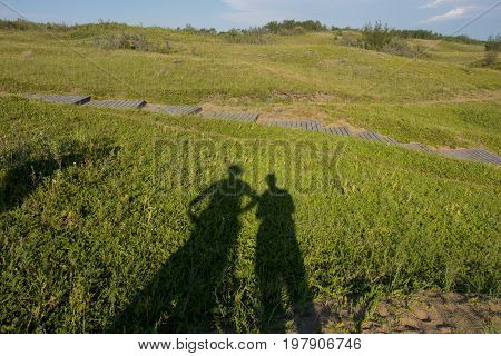 Shadows of a man and woman on a grassy hill