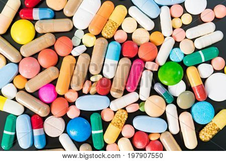 Multicolored pills and capsules on a black background