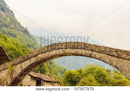 a   characteristic  bridge  of a piedmontese alpine village /a romanesque bridge made of donkey back of of the 17th century at the entrance to the village of Fondo in PiedmontItaly