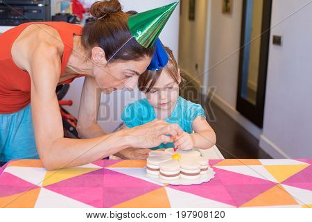 Woman And Child Putting Candle On Cake At Party