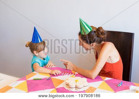 Woman Talking To Little Girl At Birthday Party