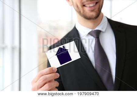 Real estate agent holding business card with drawing of house on blurred background