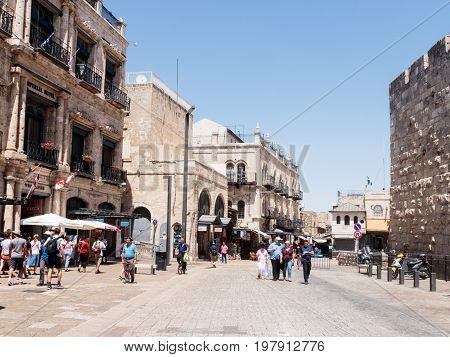 Jerusalem Israel July 14 2017 : Tourists walk along the Omar Ben el-Hatab street near the Jaffa Gates and watch the sights in the old city of Jerusalem Israel.