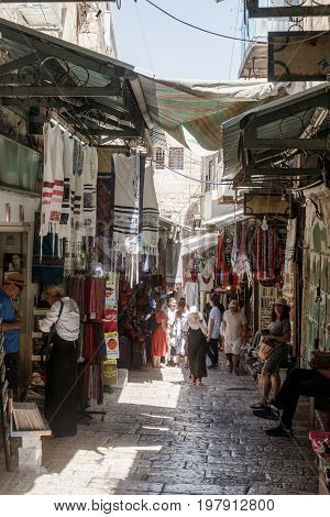 Jerusalem Israel July 14 2017 : Tourists walk through the bazaar along David Street and look at souvenirs near to Jaffa Gate in the old city of Jerusalem Israel.