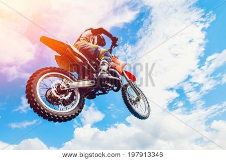 racer on a motorcycle participates in motocross in flight, jumps and takes off on a springboard against the sky. Concept active extreme rest.