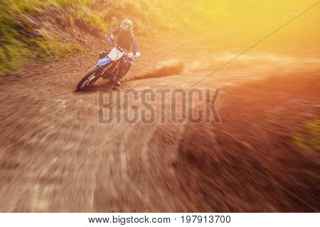 racer on a motorcycle participates in motocross comes into turn with a plume from a dirt and a dust. Concept active extreme rest.