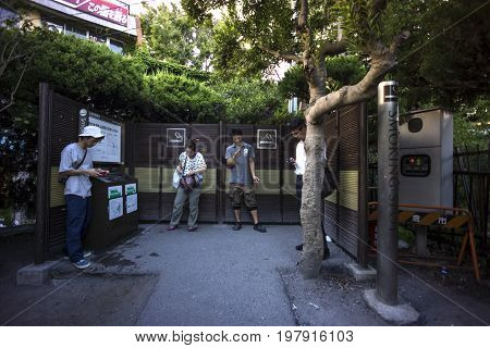 Tokio Japan August 8 2014: Smokers at a public smoking spot. Smoking facilities have been set up in several areas as a result of the antismoking trend in Japan.