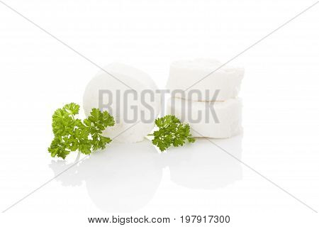Fresh goat cheese with green parsley isolated on white background. Culinary eating.