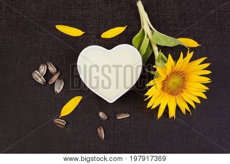 Sunflower oil from above with sunflower plant and seeds on black background.