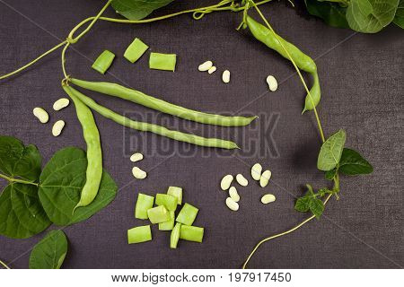 Raw green string beans whole and sliced black surface. Healthy legumes eating.