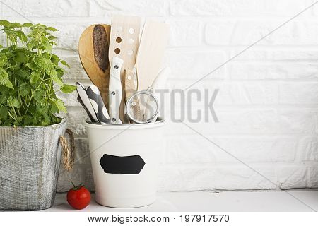 Kitchen still life on a white brick wall background: a glass with spatulas, accessories, a container with fresh mint, utensils. In the horizontal version.