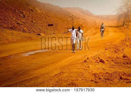 SENEGAL AFRICA - APRIL 26 2016: Unidentified young Senegalese men walking home after working on a new road in Senegal.
