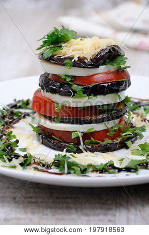 Appetizer from eggplant slices of mozzarella combined in a pile with tomatoes spilled with herbs seasoned Parmesan cheese