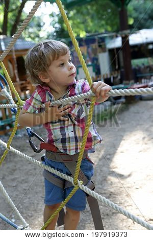 Child overcomes obstacles in the outdoor playground