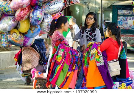 OAXACA MEXICO - MARCH 4: Girls selling traditional clothes on the street in Oaxaca Mexico on March 4 2017