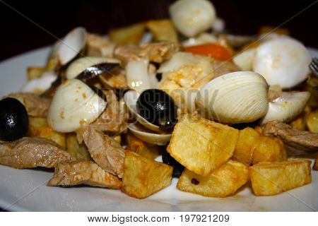 Plate of typical Portuguese dish of pork, cube cut french fries, clams, and oilives, also known as carne de porco a alentejana