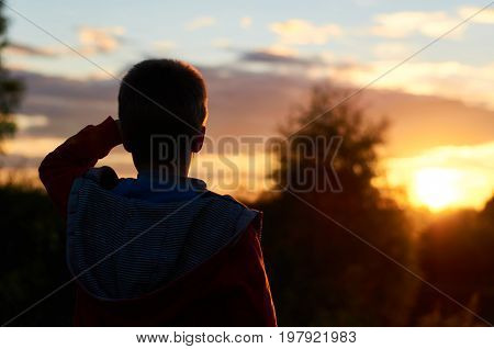 The silhouette of a child standing at sunset near the river and looking into the distance put his hand to his head. The concept of dreams and journeys