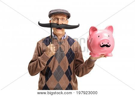 Elderly man with fake moustache holding a piggybank with fake moustache isolated on white background