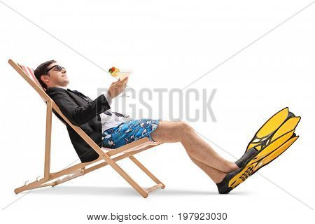 Businessman with swimming fins and a cocktail relaxing in a deck chair isolated on white background