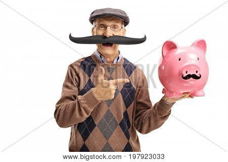 Elderly man with fake moustache pointing at a piggybank with fake moustache isolated on white background