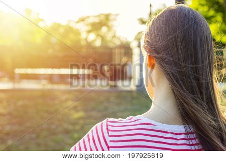 Summer sunny day. Back view. Young girl sits in a park on a bench and reads a book. The girl works studies learning keeps a diary. Lifestyle.